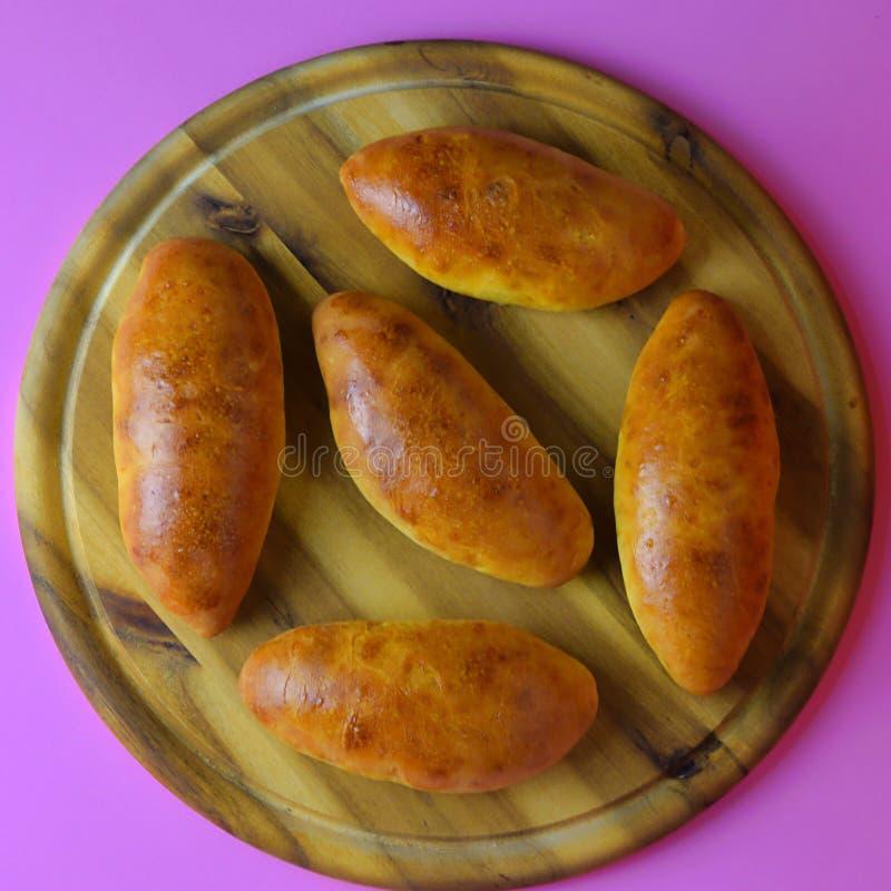 Russische pasteitjes met ui en eieren op de houten plaat royalty-vrije stock afbeelding