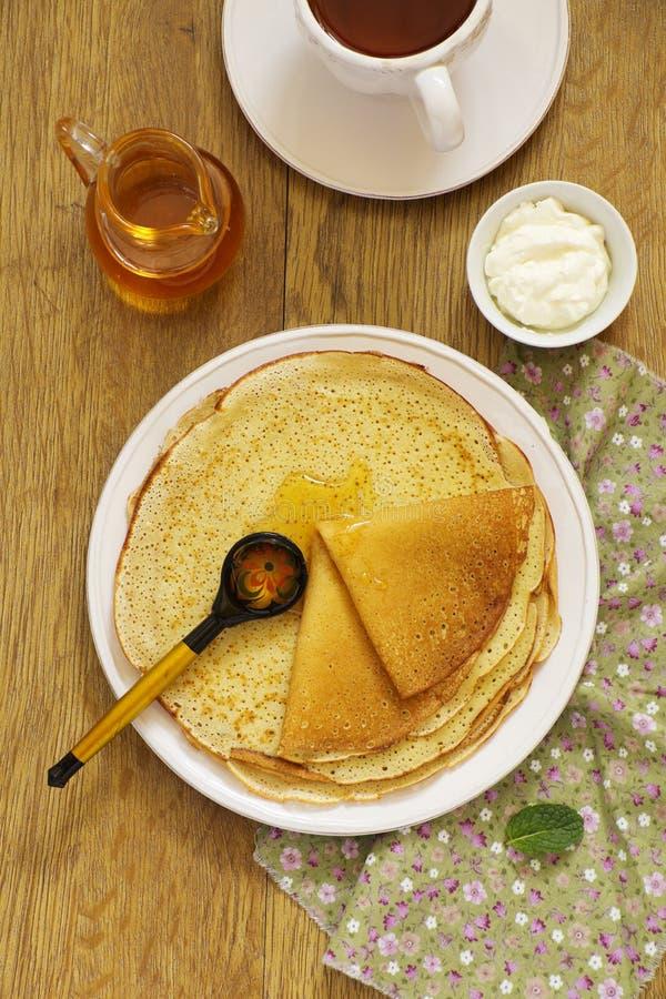 Russische Pfannkuchen mit Honig stockbilder