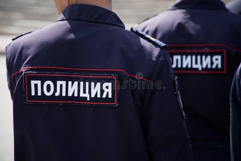 Russische Polizeibeamten während einer Patrouille auf einer Stadtstraße Ansicht von der R?ckseite lizenzfreies stockfoto