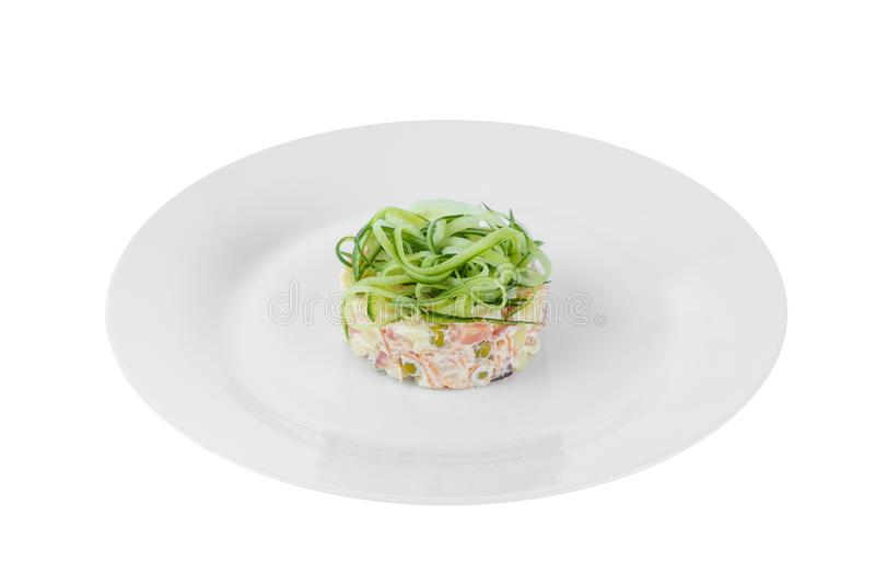 Russische salade met komkommer op geïsoleerd plaatwit royalty-vrije stock afbeelding