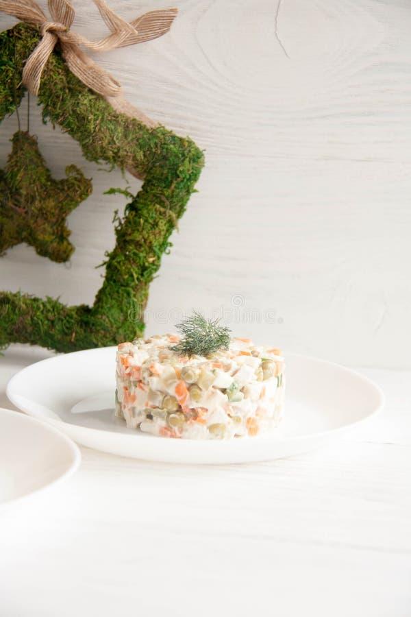 Russische salade op een witte plaat stock foto