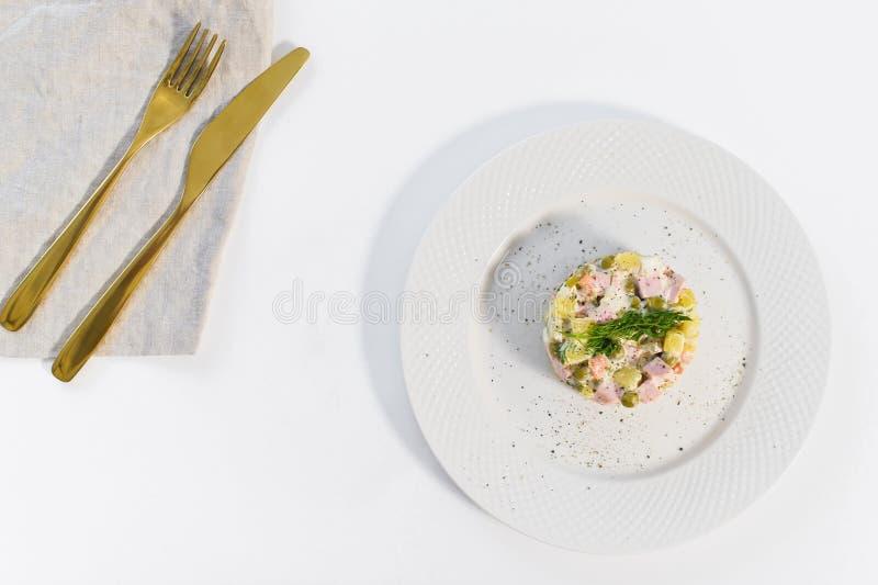 Russische salade op een witte plaat met een Gouden mes en vork op een witte achtergrond royalty-vrije stock fotografie