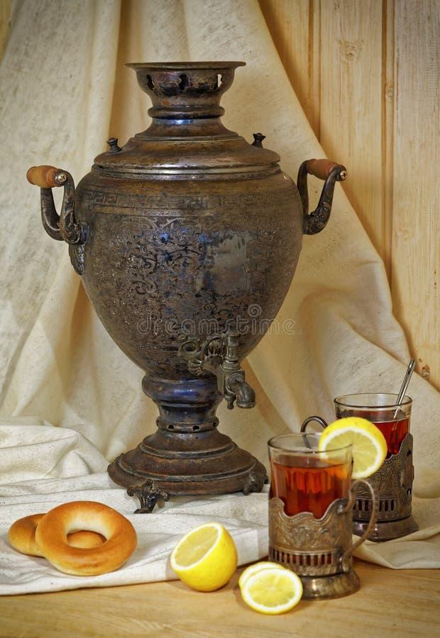 Russische samovar, thee met citroen in gefacetteerde glazen met kophouders en bublik Gekleurde foto in uitstekende stijl royalty-vrije stock afbeeldingen
