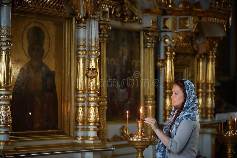 Russische schöne kaukasische Frau mit dem roten Haar und einem Schal auf ihrem Kopf ist in der orthodoxen Kirche, Lichter ein Ker lizenzfreie stockbilder