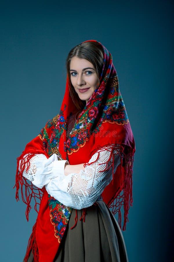 Russische schoonheidsvrouw in de nationale gevormde sjaal op blauwe grijze achtergrond Maslenitsa stock foto's