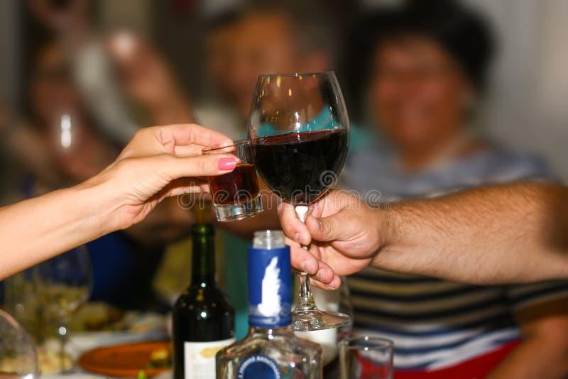 Russische traditie aan gerinkelglazen tijdens de vakantie Een vrouw met een glas van de glazen van cognacgerinkels met een man me royalty-vrije stock afbeelding