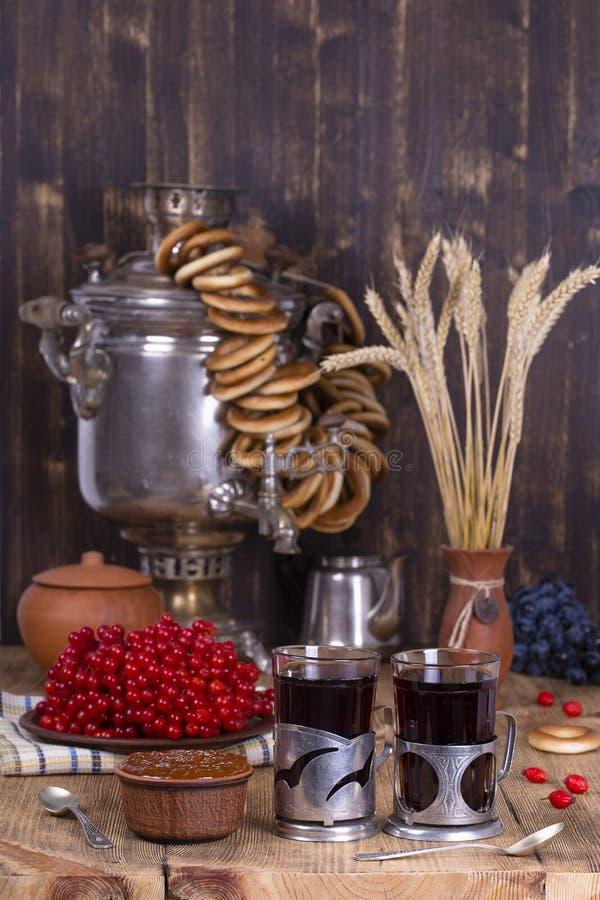 Russische traditionele ketelsamovar op de houten lijst Zwarte thee, ongezuurde broodjes, rode viburnum, jam en theesamovar in de  royalty-vrije stock foto's