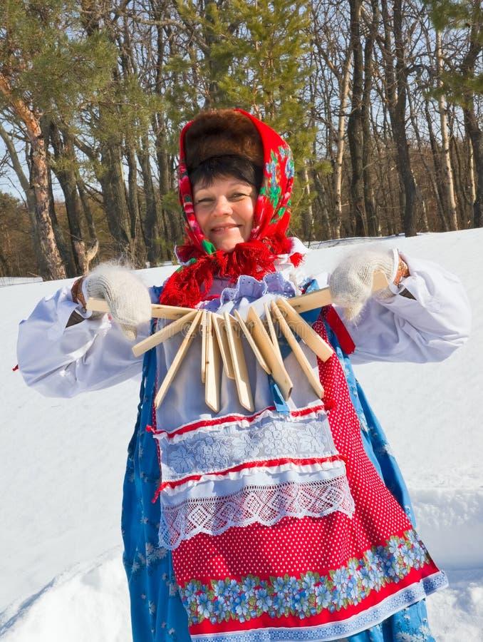 Russische vrouw in sundress met houten rammelaar stock foto's
