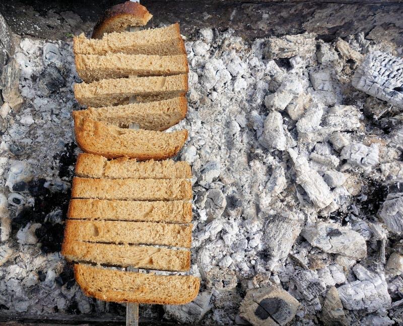 Russische Weise, Brot auf den Kohlen zu grillen stockfotografie