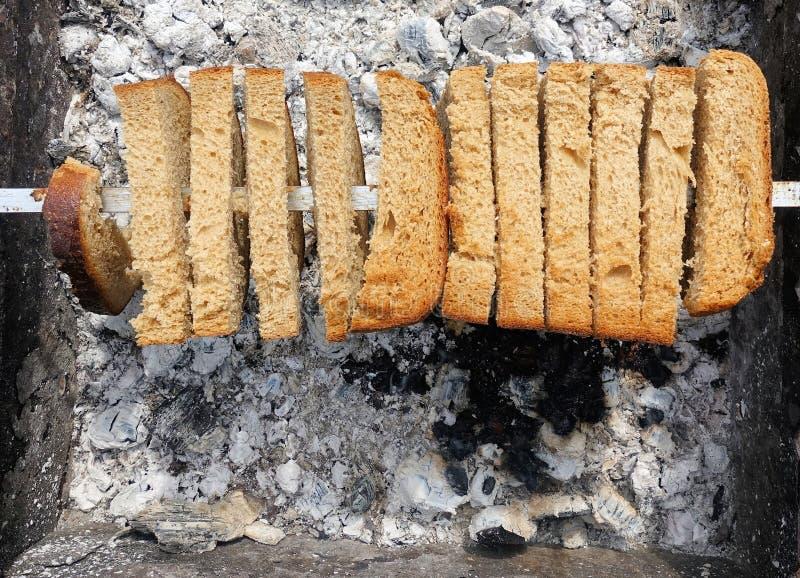 Russische Weise, Brot auf den Kohlen zu grillen lizenzfreies stockbild