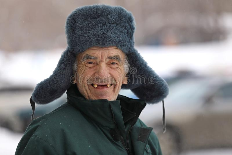 Russischer alter Mann im Winterhutlächeln lizenzfreie stockbilder