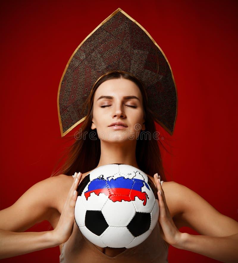 Russischer Art Fansport-Frauenspieler im kokoshnik Hut-Grifffußball das glückliche Lächeln mit Kopienraum des freien Texts auf Ro lizenzfreie stockfotos