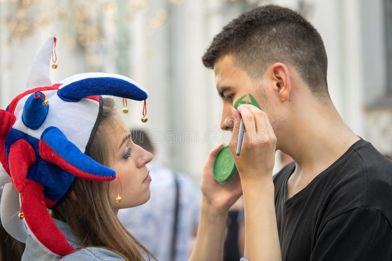Russischer Mädchensportfreund in einem bunten Hut, der brasilianische Flagge auf der Backe des brasilianischen Mannes zeichnet lizenzfreies stockfoto