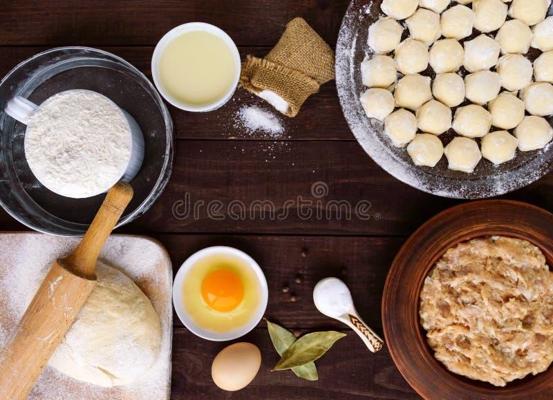 Russischer traditioneller Teller - pelmeni (saftiges Hackfleisch mit Gewürzen im Teig) Bestandteile für das Kochen stockfotografie