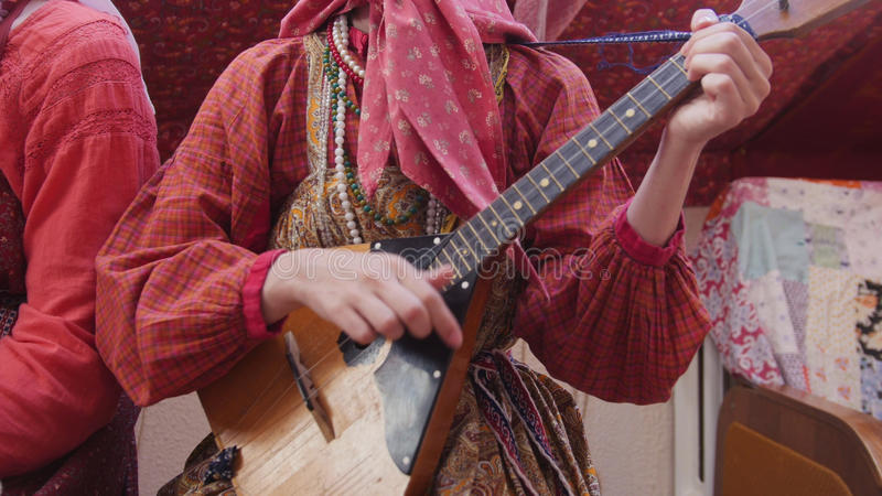 Russisches Ensemble der Volksmusik - Frau im russischen Volkskostüm, welches die Balalaika spielt lizenzfreie stockfotos