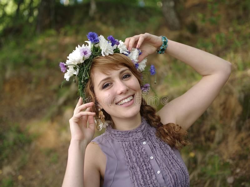 Russisches Mädchen mit einem Blumenkranz lizenzfreies stockbild