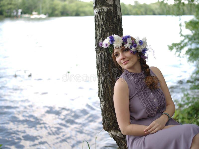 Russisches Mädchen mit einem Blumenkranz lizenzfreie stockfotos