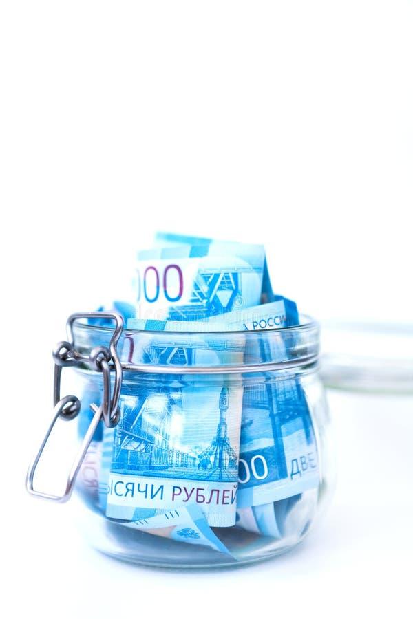 Russisches Papiergeld Neue russische Banknoten von 2000 zwei Tausende-Rubeln schließen oben im Glasgefäß auf Weiß lokalisiertem H stockfotografie