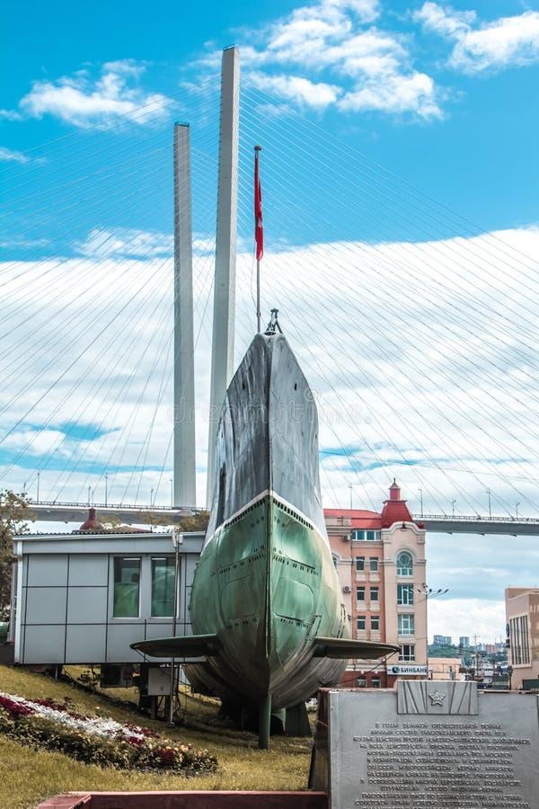 Russisches Unterseeboot auf dem Hintergrund der Schrägseilbrücke von Wladiwostok stockbilder