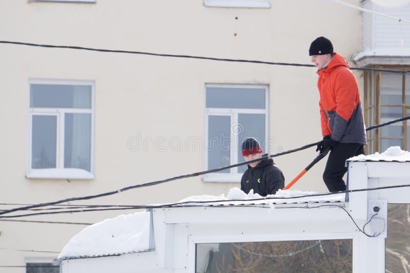 Russland Berezniki am 13. März 2018: Junger Mann mit showel arbeitet an Scheunendach entfernen den Schnee stockfotos