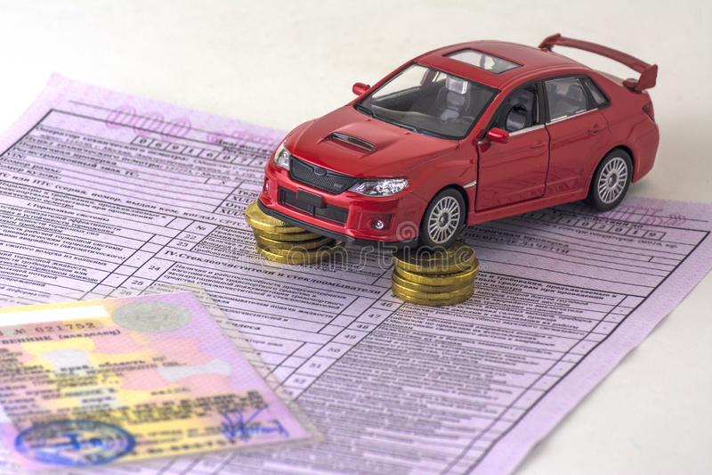 Russland, Diagnosekarteninspektionsmaschine, Autoversicherung Abschluss oben Das rote Auto ist auf den Spalten von Münzen Zertifi stockfotografie