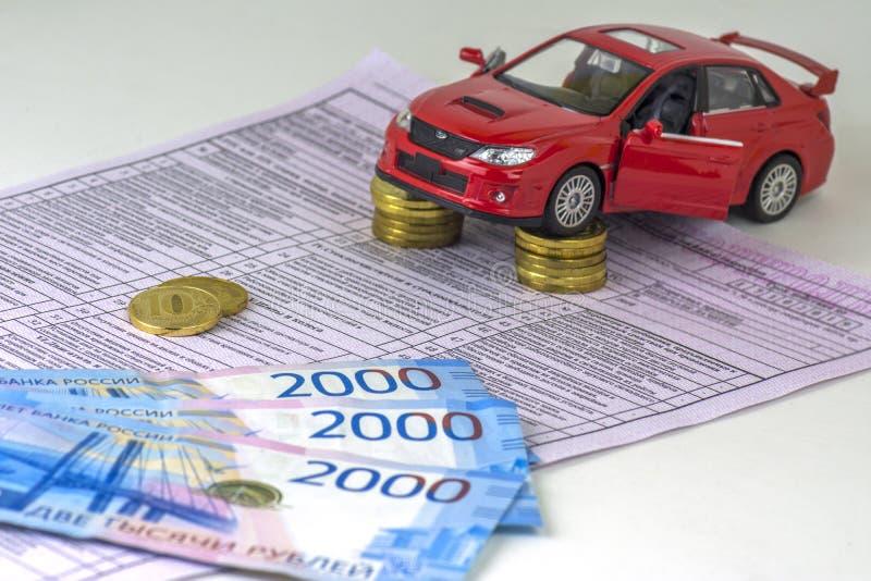 Russland, Diagnosekarteninspektionsmaschine, Autoversicherung Das rote Auto ist auf den Spalten von Münzen Wert einiger russische lizenzfreie stockfotografie