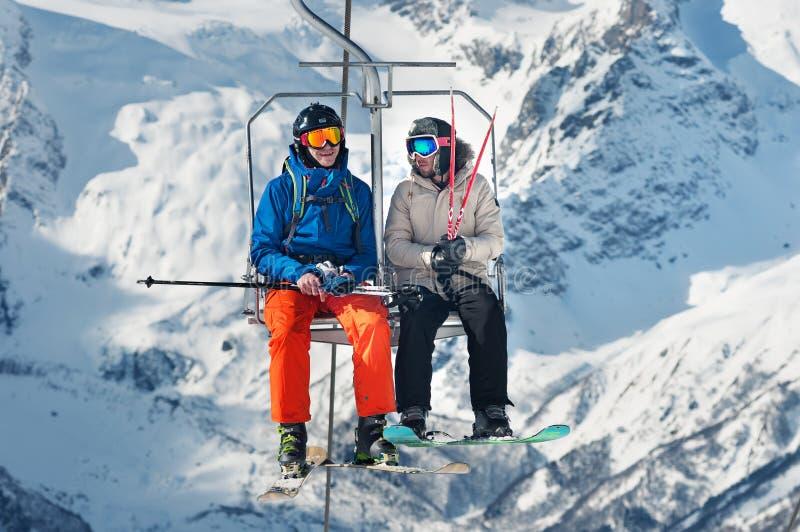 Russland, Dombai- 7. Februar 2017: Zwei Skifahrer heben zum Ski Resort-Hoch in den Winterschneebergen an der StuhlDrahtseilbahn a lizenzfreie stockfotografie