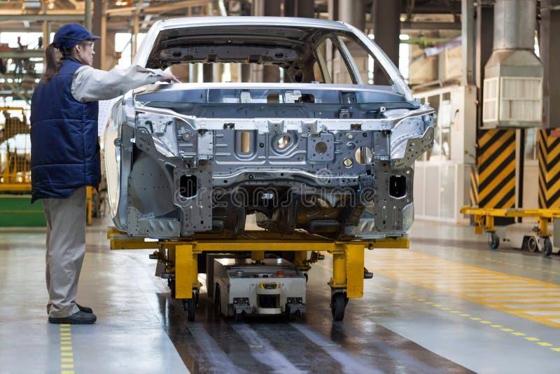Russland, Izhevsk - 15. Dezember 2018: LADA Automobile Plant Izhevsk Die Arbeitnehmerin überprüft den Körper eines Neuwagens lizenzfreie stockfotos