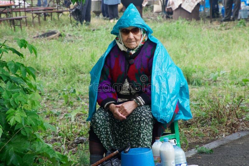 Russland, Magnitogorsk, - Juni, 15, 2019 Eine ältere Frau verkauft Milch in den Plastikflaschen auf der Seite der Straße lizenzfreie stockfotografie