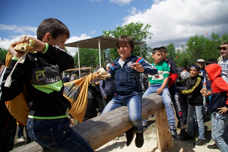 Russland, Magnitogorsk, - Juni, 15, 2019 Kinder kämpfen leichtsinnig mit Taschen auf einem Klotz während des Feiertags Sabantuy e stockfotografie