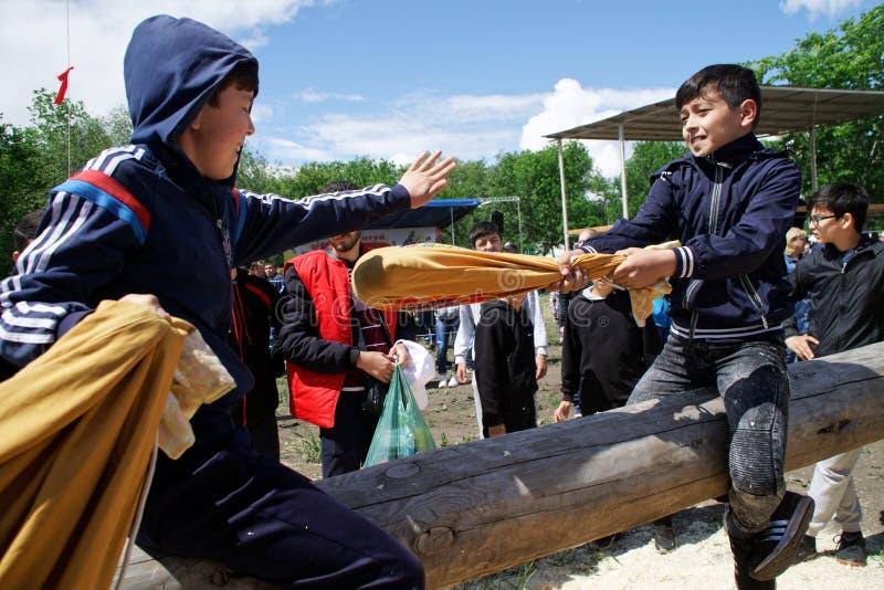 Russland, Magnitogorsk, - Juni, 15, 2019 Kinder kämpfen mit Taschen auf einem Klotz während des Feiertags Sabantuy Nationales Spi lizenzfreies stockfoto