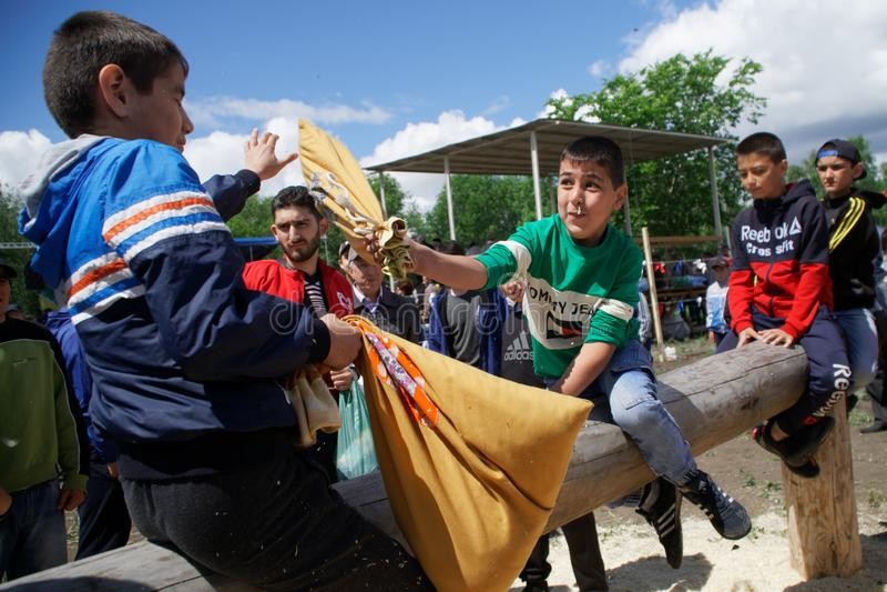 Russland, Magnitogorsk, - Juni, 15, 2019 Nationales Turkic-Spiel - Kampf mit Säcken auf einem Klotz während des Feiertags Sabantu stockbilder