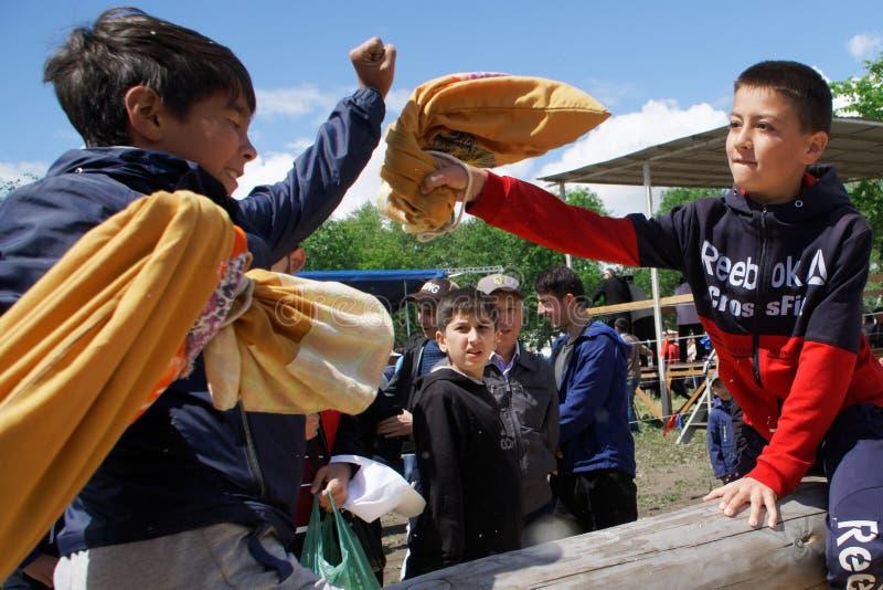 Russland, Magnitogorsk, - Juni, 15, 2019 Zentrales asiatisches traditionelles aktives Spiel - Kampf mit Taschen auf einem Klotz w stockfotos