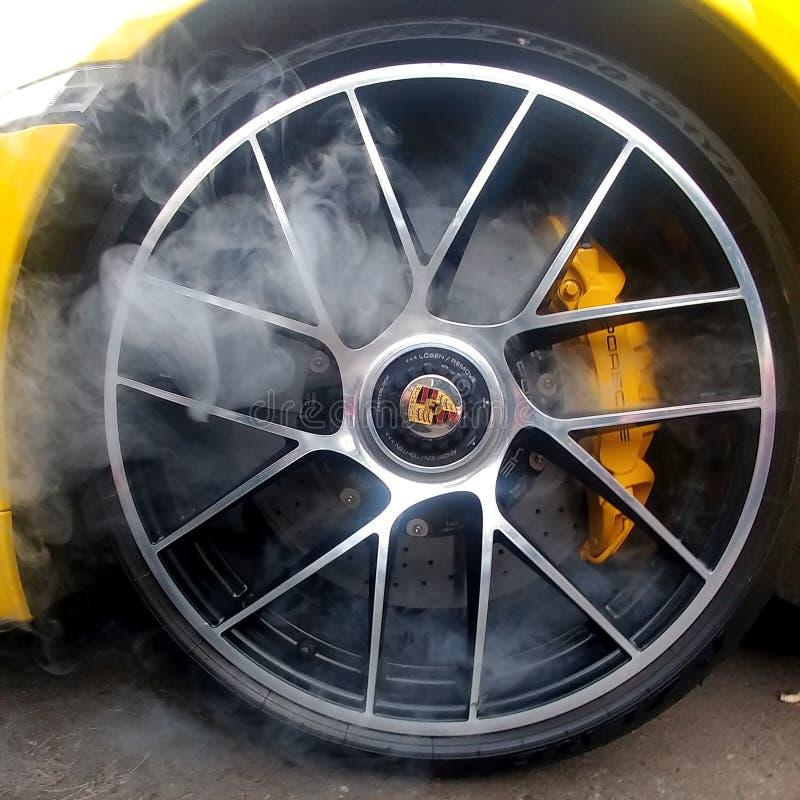 Russland, Moskau - 4. Mai 2019: Gelbes Porsche 911 Leichtmetallfelgen Turbos S mit keramischen Bremsen des Kohlenstoffs und Rauch stockfotografie