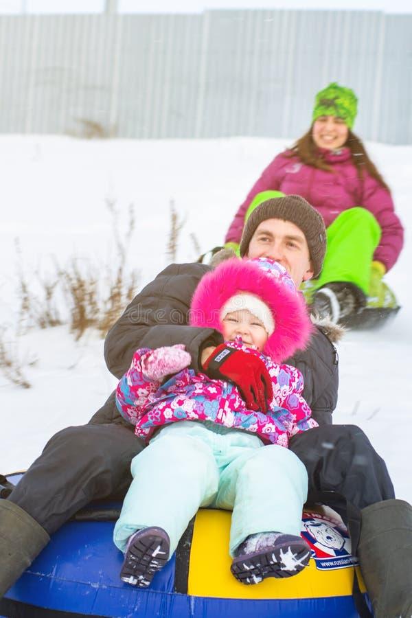 Russland, Ryazan am 5. Januar 2019: glücklicher Mann mit seiner Familie, die hinunter Hügel auf Schneerohren über natürlichem stockbilder