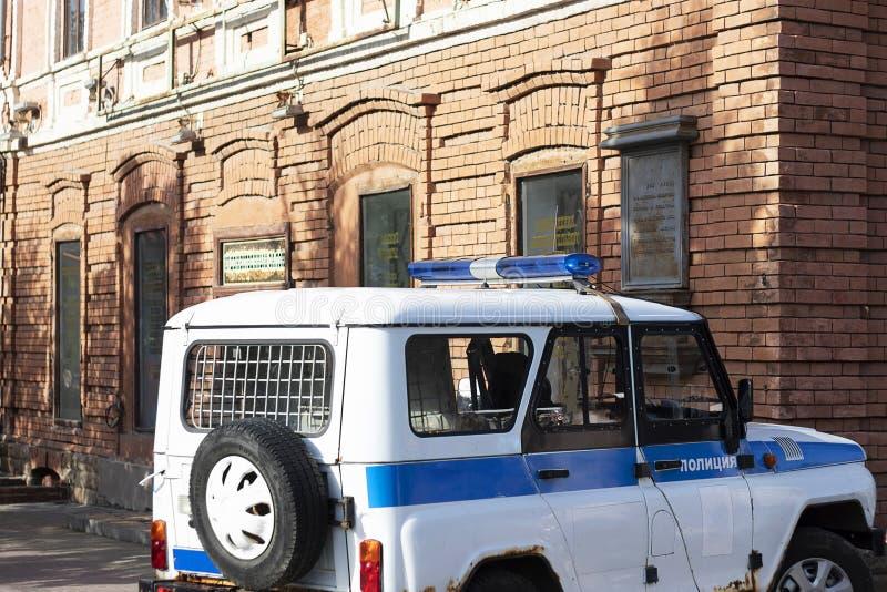 Russland, Tscheljabinsk, 12-06-2019 UAZ Redaktionell steht EIN UAZ-Polizeiwagen mit einer blauen Sirene nahe der roten Wand Strei lizenzfreie stockbilder