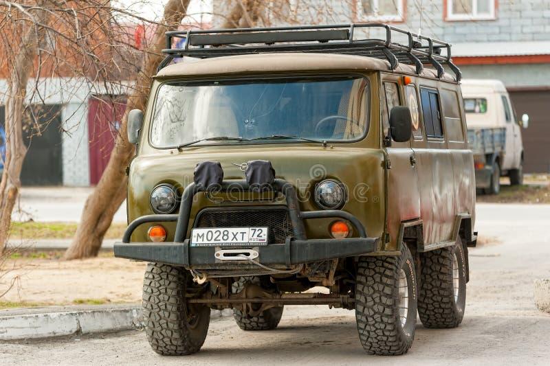 Russo brutal fora do carro UAZ da estrada na cidade foto de stock