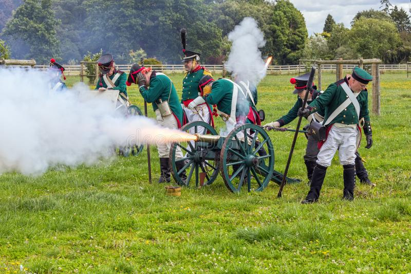 Russo Prussian Artillery, Napoleonic Wars. Re-enactors dressed as Russo Prussian Artillery Soldiers firing their cannon during a battle in the Napoleonic Wars royalty free stock photo