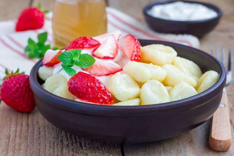 Russo tradicional, requeijão ucraniano & x22; lazy& x22; as bolinhas de massa serviram com iogurte, mel e morango fotos de stock