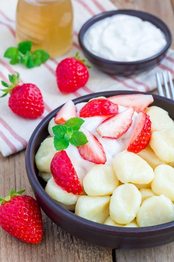 Russo tradicional, requeijão ucraniano & x22; lazy& x22; as bolinhas de massa serviram com iogurte, mel e morango fotos de stock royalty free