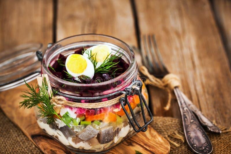 Russo tradicional salada mergulhada do betroot e de arenques sob um f fotos de stock