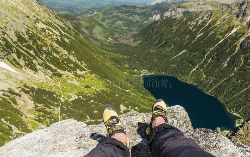 Rust bij de bovenkant na het beëindigen van de het beklimmen route Het beklimmen van schoenen op de voeten stock foto's