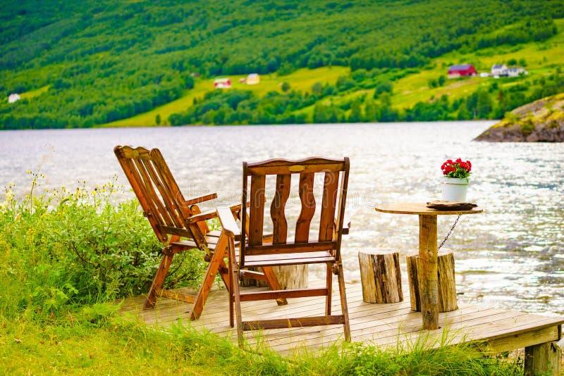 Rust de picknick van het eindegebied chaires op de kust van het fjordmeer royalty-vrije stock afbeelding