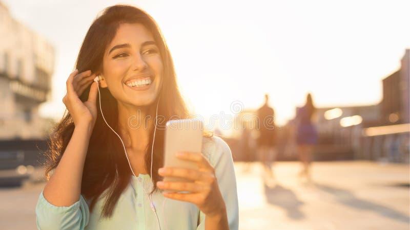 Rust in de stad Vrouw het luisteren muziek op telefoon stock foto