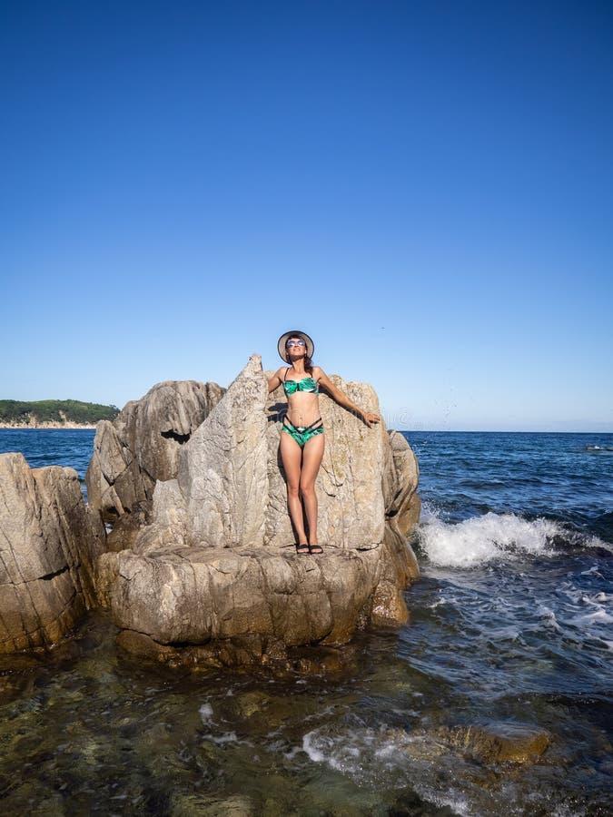 Rust door het overzees: Een meisje in een badpak, zonnebril en een hoed bevindt zich op een rotsachtige kust royalty-vrije stock fotografie