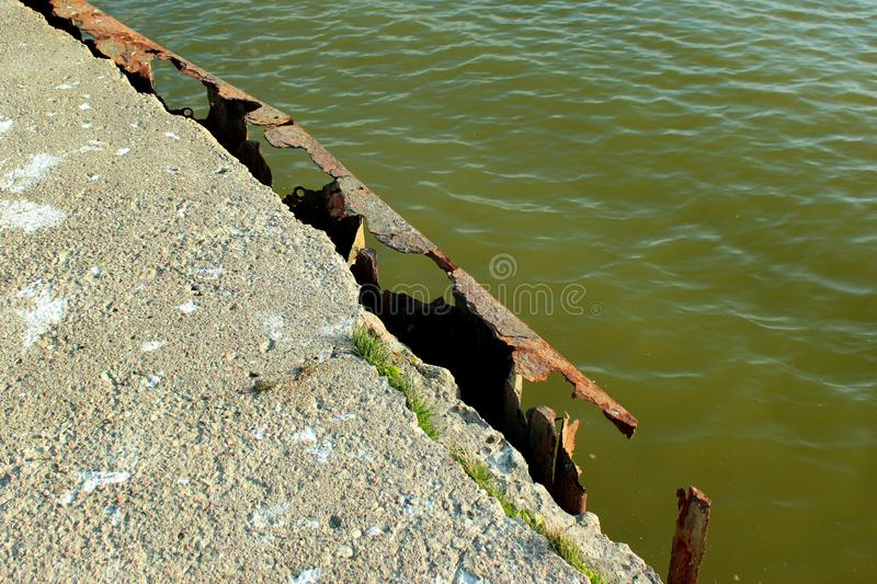 Rust-eaten iron frame of an old concrete pier royalty free stock image