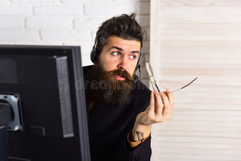Rust en beroeps Gebaarde mens die in bureau werken Mens met lange baard en hoofdtelefoons Gebaarde bedrijfvertegenwoordiger stock foto