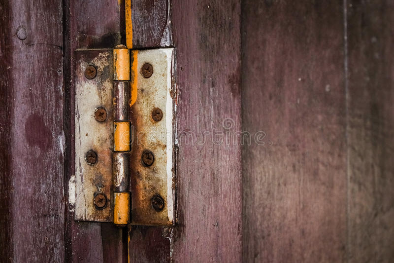 A rust hinge at the old wooden door. royalty free stock photography