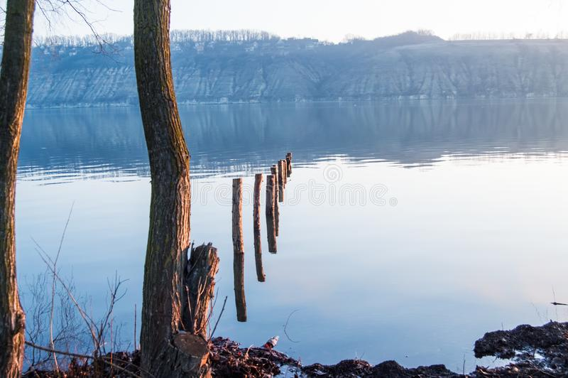 Rust of kalmte van water op brede rivier in de vroege ochtend Kalme oppervlakte van rivier met hoog tegenover bank in blauwe neve stock afbeelding