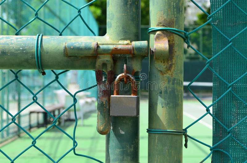 Rust lock at old green wire mesh fence in front of tennis court stock images